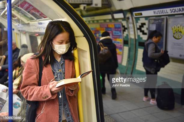 Woman reads a book while wearing a face mask on the Picadilly Line tube train on March 02, 2020 in London, England. There has been thirteen more...