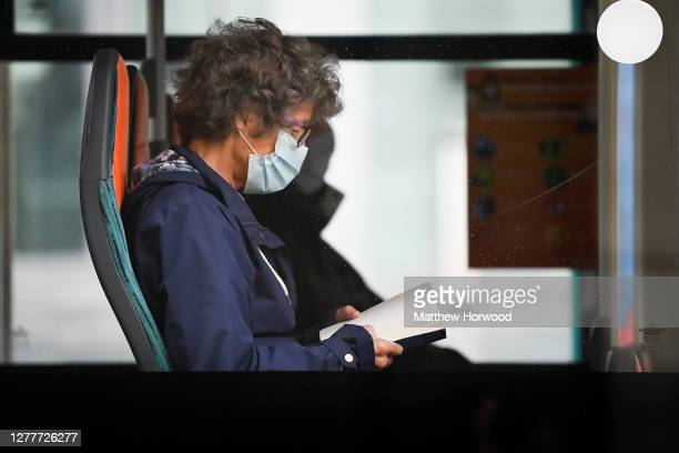 Woman reads a book while wearing a surgical face mask on a Cardiff Bus on September 3, 2020 in Cardiff, Wales.