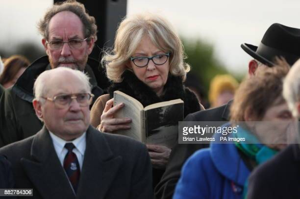 A woman reads a collection of Patrick Kavanagh poems as she attends the Patrick Kavanagh Graveside Tribute in Inniskeen on the 50th anniversary of...