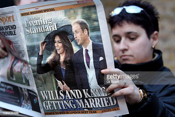 A woman reads a copy of the Evening Standard newspaper outside Clarence House shortly after the announced engagement of Prince William and Kate...