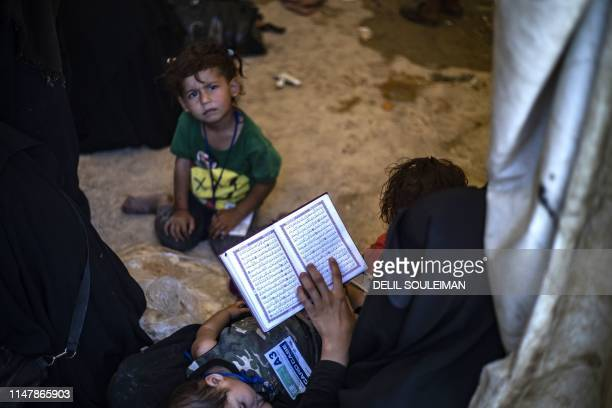 A woman reads a copy of the Koran as a child looks on at the AlHol camp in northeastern Syria's AlHasakeh governorate on June 3 as Kurdish...