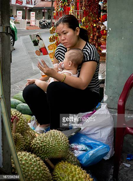 CONTENT] A woman reads a magazine with her baby in her lap as she waits for customer at her jack fruit stall in Ho Chi Minh City