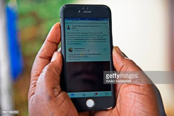 A woman reads a message on social media tax as she scrolls through her Facebook account on her phone in Kampala on July 5 2018 Politicians clerics...