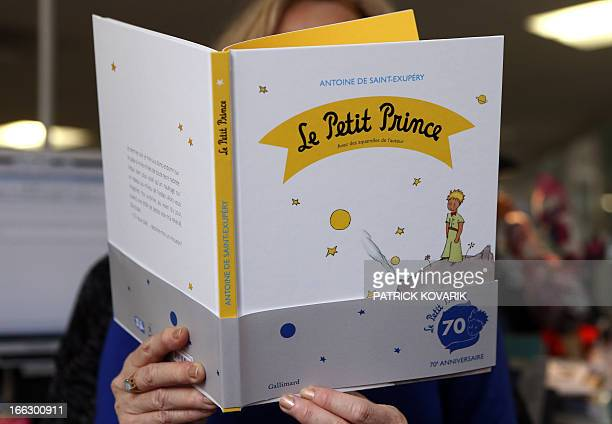 A woman reads a new edition of The Little Prince book on April 11 2013 in Paris France is marking the 70th anniversary of the worldloved The Little...