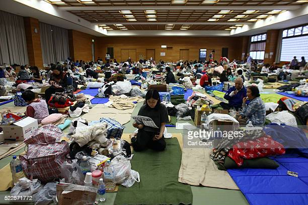 Woman reads a newspaper as she shelters, along with others, in a gymnasium used as an evacuation centre following an earthquake, on April 20, 2016 in...