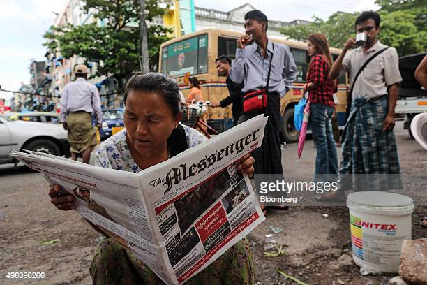A woman reads a newspaper at a bus station in Yangon Myanmar on Monday Nov 9 2015 The spirit of NLD supporters was running high as some 10000 backers...