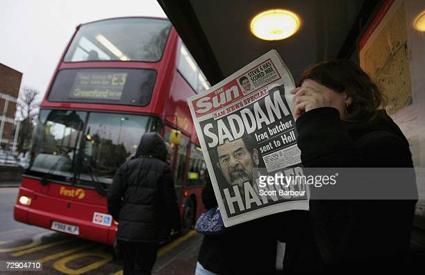A woman reads a newspaper at a bus stop with a headline of the death of former Iraqi president Saddam Hussein on December 30 2006 in London England...