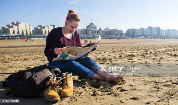 A woman reads a newspaper on the Scheveningen beach on March 5 2014 Spring like weather is expected in the country for the next week AFP PHOTO / ANP...