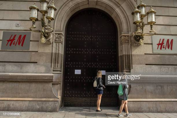 A woman reads a note in a HM fashion store closed as measure against the coronavirus expansion on March 14 2020 in Barcelona Spain The Catalan...