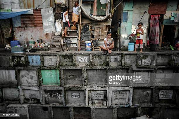 A woman reads a pocketbook outside their makeshift house atop stacked graves at the municipal cemetery of Navotas city north of Manila Philippines...