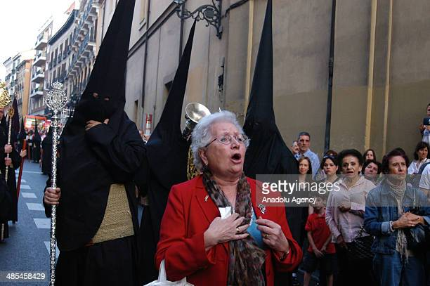 A woman reads a poem for Jesus as Catholics walk during the silence procession of Maundy Thursday in Madrid Spain on April 18 2014 Easter is a...