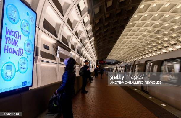 A woman reads a public awareness sign in response to the COVID19 coronavirus outbreak as she waits for a train in the DC Metro in Washington DC on...