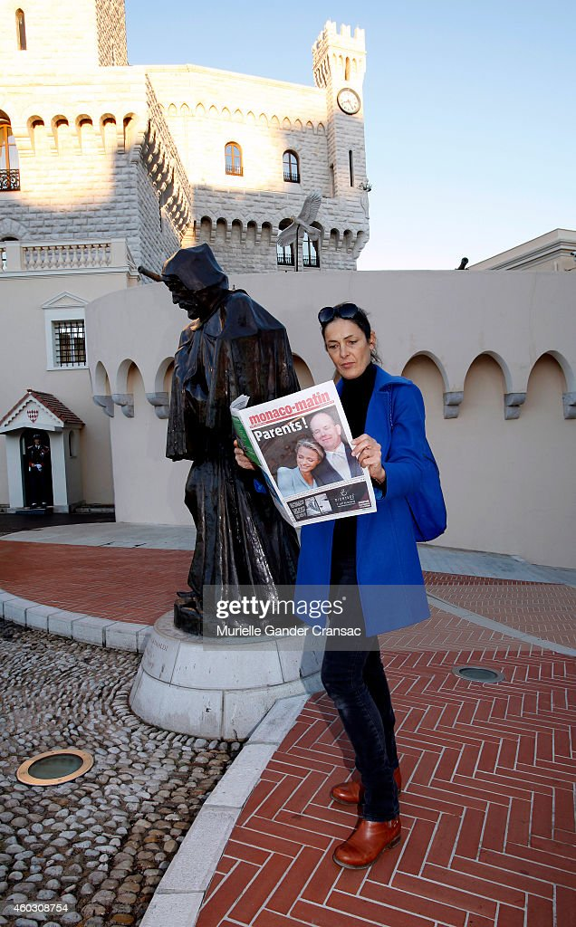A woman reads an article about yesterday's birth of the royal twins Prince Jacques and Princess Gabriella outside the Monaco Palace on December 11, 2014 in Monaco, Monaco.