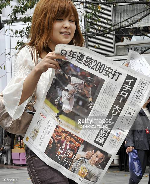 A woman reads an extra edition newspaper carrying coverage of the Seattle Mariners' Japanese slugger Ichiro Suzuki in Tokyo on September 14 2009...