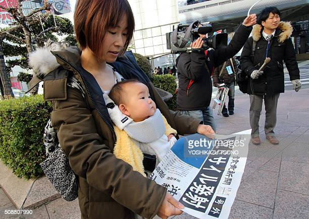 A woman reads an extra edition newspaper in Tokyo which report about North Korea's rocket launch on February 7 2016 North Korea launched a longrange...