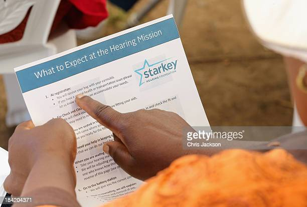 A woman reads an information sheet before having hearing aids fitted by the Starkey Foundation at Lesotho Cooperative College on October 10 2013 in...