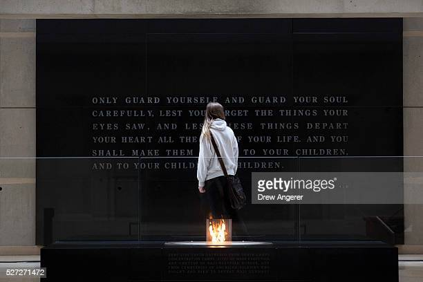 A woman reads an inscription near the eternal flame during the annual Names Reading ceremony to commemorate those who perished in the Holocaust in...