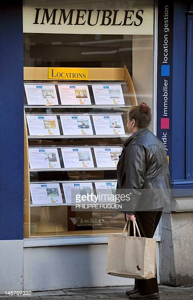 A woman reads anouncements of a real estate agent on January 30 2012 in Lille northern France The French construction industry is set to shed 35000...