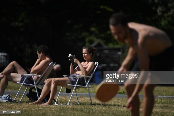 Woman reads as people enjoy the sunny weather in Shoreditch Park in London on May 30 ahead of the coming into force of the first significant easing...