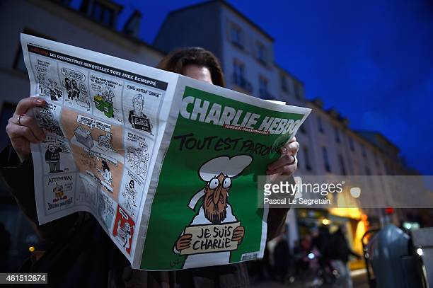 A woman reads Charlie Hebdo on January 14 2015 in Saint Germain en Laye France Three million copies of the controversial magazine have been printed...