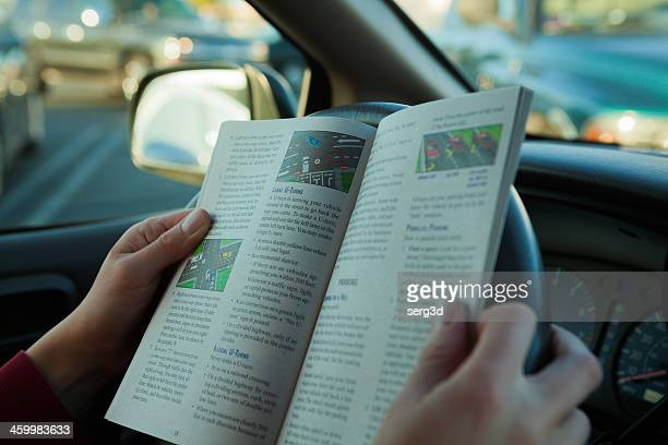 Woman reads driving book in a car