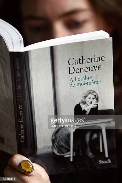 A woman reads French star Catherine Deneuve's diary A l'Ombre de MoiMeme 20 April 2004 in Paris on the eve of its release The book is a collection of...