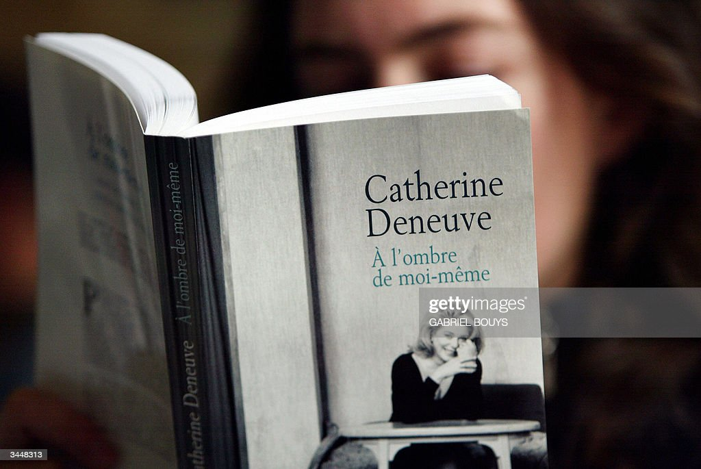 A woman reads French star Catherine Dene : News Photo