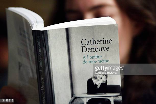 A woman reads French star Catherine Deneuve's diary 'A l'Ombre de MoiMeme' 20 April 2004 in Paris on the eve of its release The book is a collection...