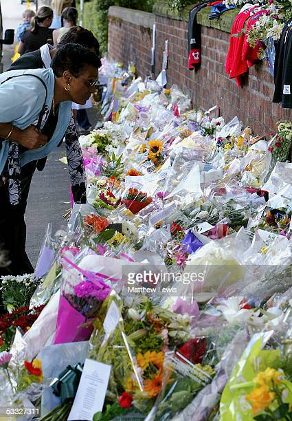 A woman reads inscriptions on cards among floral tributes at the scene where 18yearold Anthony Walker died near McGoldrick Park Huyton on August 5...