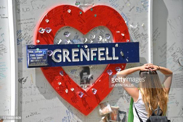 A woman reads messages of support written on the wall surrounding Grenfell tower in west London on June 14 on the third anniversary of the highrise...