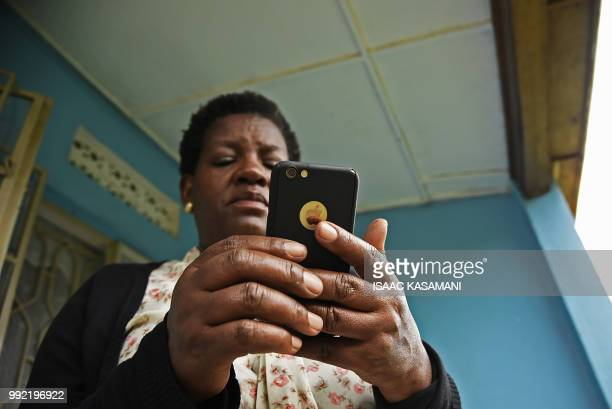 A woman reads messages on her Apple iphone in Kampala on July 5 2018 Politicians clerics feminists and others have formed a broad coalition of...