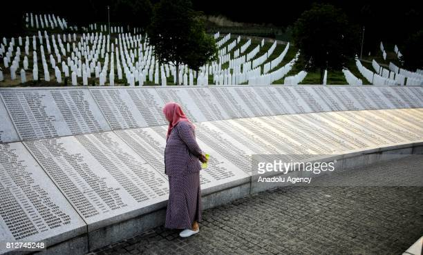 A woman reads name of the victims on the memorial at the Potocari Memorial Cemetery in Srebrenica Bosnia and Herzegovina on the 22nd anniversary of...