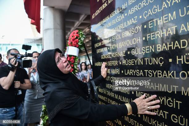 A woman reads names on a commemorative plaque as relatives of victims attend a memorial ceremony on June 28 2017 at Ataturk International airport in...