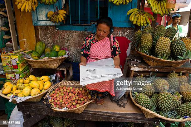 A woman reads newspaper while selling fruits at Iewduh Bazar in Shillong Meghalaya Lewduh also known as Bara Bazar is a bustling marketplace in...