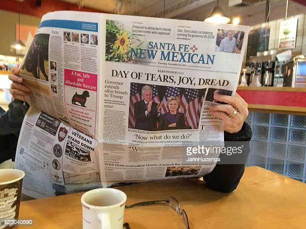 "woman reads newspaper with headline: ""day of tears, joy, dread"" - donald trump us president photos stock photos and pictures"