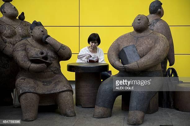 A woman reads on her mobile phone next to sculptures by artist Rosanna Li Weihan outside an MTR station in Hong Kong on September 6 2014 Hong Kong's...