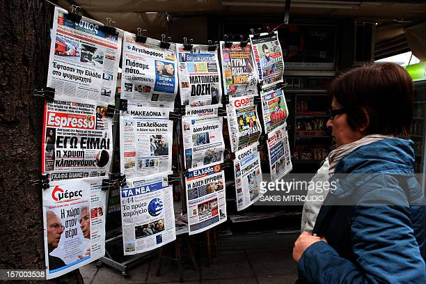 A woman reads on November 27 2012 newspapers' headlines in Thessaloniki The eurozone and IMF saved Greece with a redrawn rescue to avert bankruptcy...