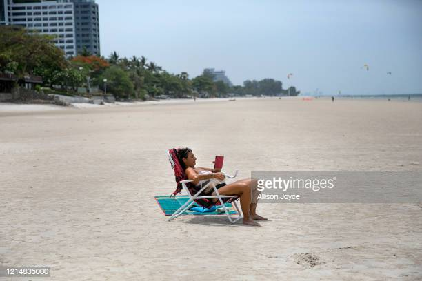 Woman reads on the beach on May 24, 2020 in Hua Hin, Thailand. As the province of Prachuap Khiri Khan signed orders to re-open hotels last week,...