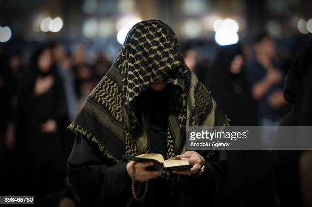 A woman reads Quran as Iranian worshipers pray at Mosalla Mosque on the 21th day of Ramadan as eventual Laylat alQadr one of the Muslim's holiest...