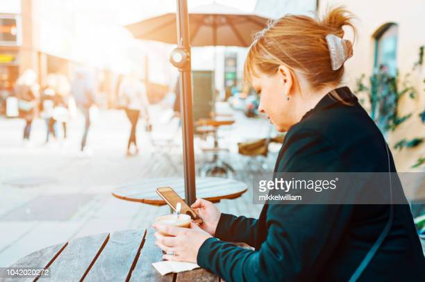Woman reads text message on her smart phone while sitting at outdoor cafe