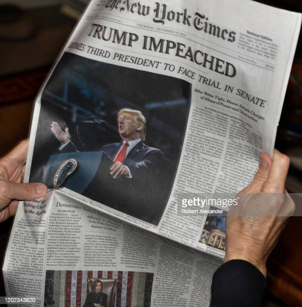 A woman reads the front page of the December 19 2019 New York Times with its headline reporting the impeachment of US President Donald Trump by the...