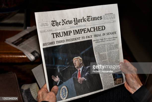 Woman reads the front page of the December 19, 2019 New York Times with its headline reporting the impeachment of U.S. President Donald Trump by the...