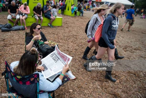 A woman reads the Glastonbury Free Press with the headline 'See you in 731 days' at Glastonbury Festival Site on June 25 2017 in Glastonbury England...