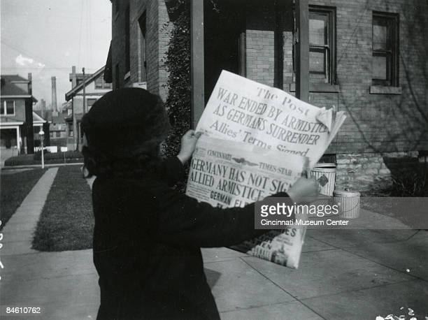 Woman reads the headlines of the local papers 'The Cincinnati Times Star' and 'The Post' proclaiming that an armistice has been signed ending the...