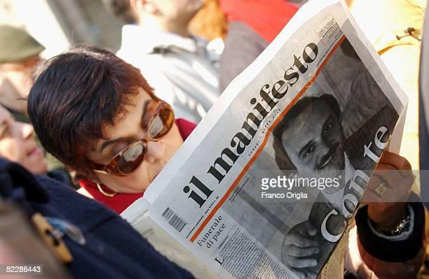 Woman reads the Italian journal Il Manifesto showing Italian intelligence officer Nicola Calipari on the front cover outside Santa Maria Degli Angeli...