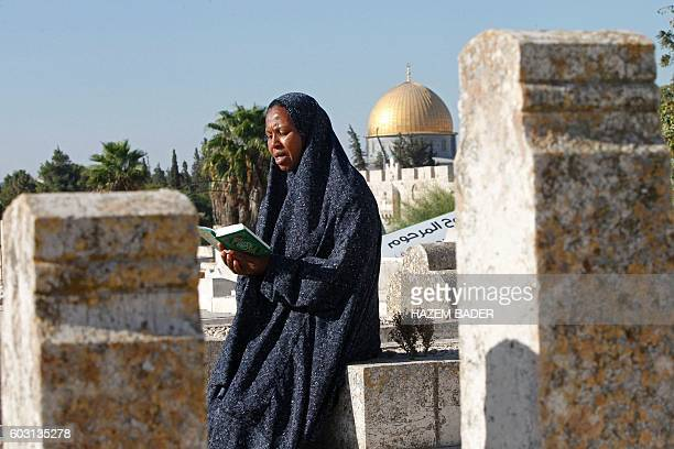 A woman reads the Koran over the grave of a loved one at a Muslim cemetery near the AlAqsa Mosque compound in Jerusalem's Old City on September 12 on...
