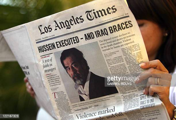 A woman reads the Los Angeles Time newspaper headlining the execution of former Iraqi president Saddam Hussein 30 December 2006 in Los Angeles Saddam...