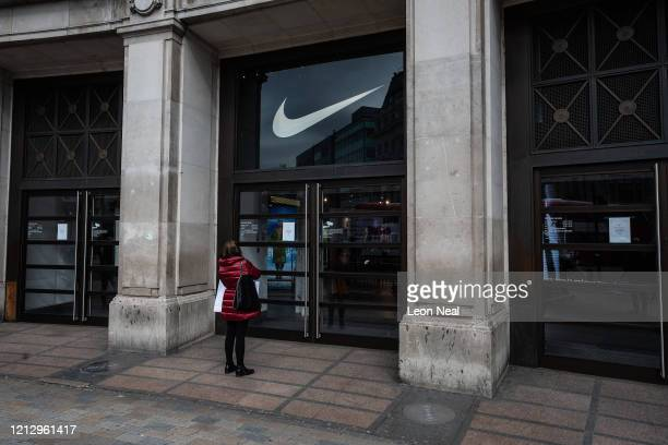 Woman reads the sign on the door of the closed Niketown store on Oxford Street on March 17, 2020 in London, England. Boris Johnson held the first of...