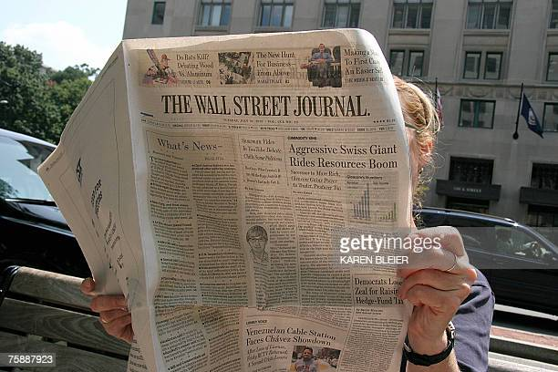 A woman reads the Wall Street Journal while siiting on K Street 31 July 2007 in Washington DC Rupert Murdoch's News Corp appears to have won...