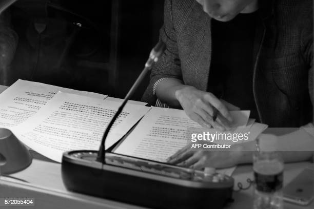 A woman reads translation from a booth as US President Donald Trump and Chinese President Xi Jinping speak during a joint statement in Beijing on...